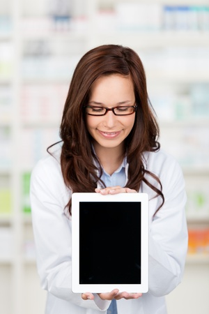 Smiling Pharmacist shows an ipad computer at the drugstore photo
