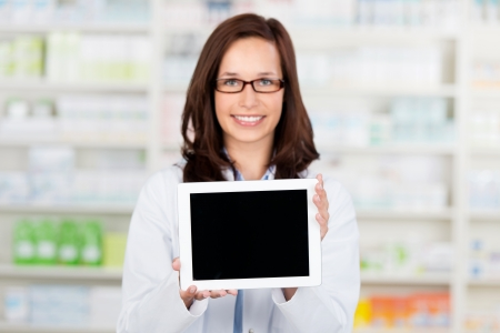 pharmacy equipment: Smiling female Pharmacist shows an ipad computer at the drugstore