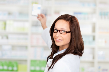 Portrait of a young female pharmacist selecting a medication Stock Photo - 21148786