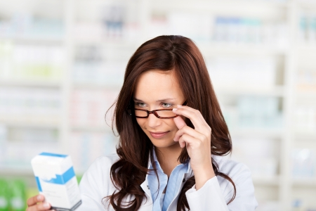 lowering: Pharmacist woman reading the medication at the drug store