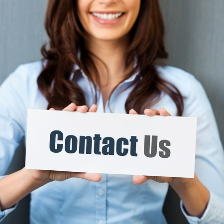 advertise with us: Smiling woman showing white card with Contact us word in a close up shot Stock Photo