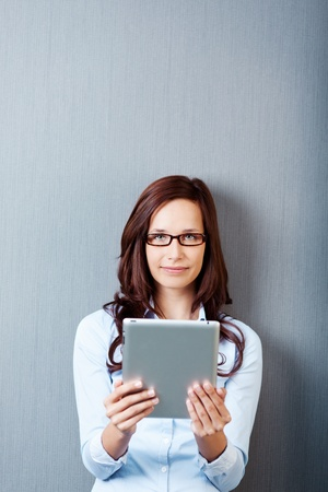 Woman with glasses holding an ipad tablet isolated on grey photo