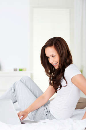 Smiling fresh woman sitting on bed while browsing the internet photo