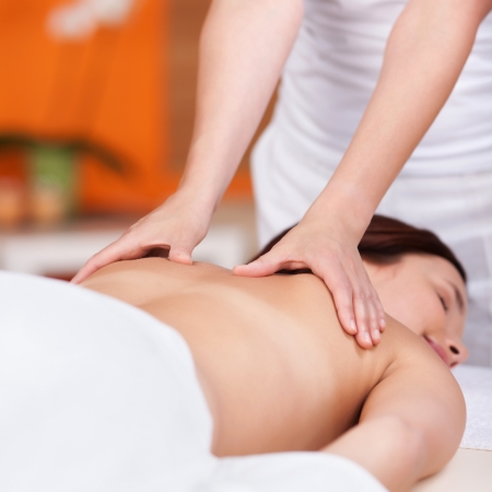 massage therapy: Masseuse is working the back of a young woman