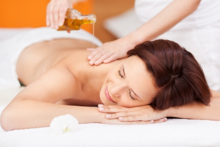 pampered: Beautiful young woman enjoying a spa beauty treatment with an oil based massage