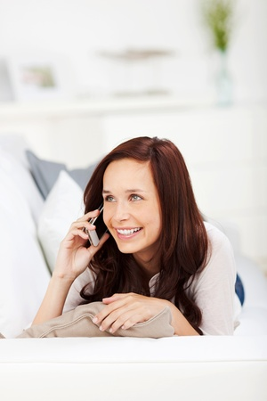 Smiling woman resting on couch while talking on the telephone photo