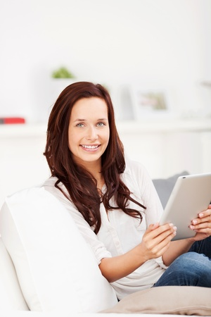 Portrait of a woman with a tablet computer looking at the camera with a lovely smile as she relaxes on a sofa Stock Photo - 21148897