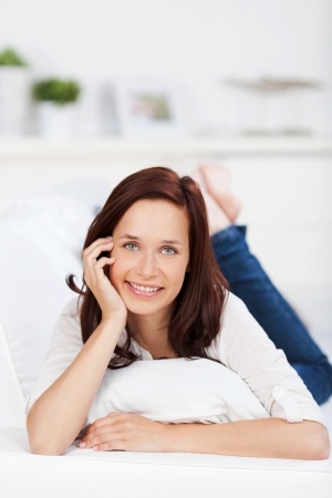 Portrait of attractive woman lying on the sofa in a front view shot Stock Photo - 21148908