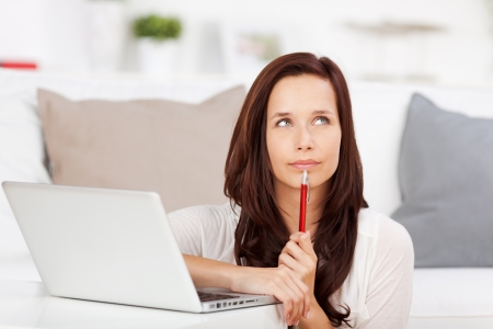 remembering: Portrait of looking up woman in front of laptop at home