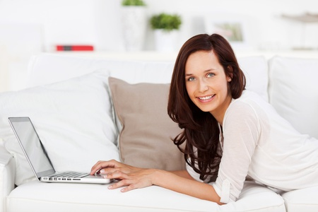 Attractive young woman lying on couch while searching using a laptop photo