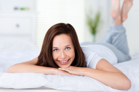 Smiling woman lying on her bed on her stomach facing the camera relaxing while enjoying a lazy day photo