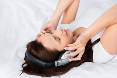 letras musicales: Mujer que se relaja escuchando meditaciones a través de sus auriculares