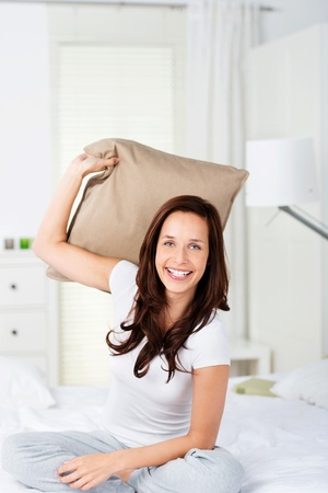 Beautiful brunette woman in a pillow fight at home photo