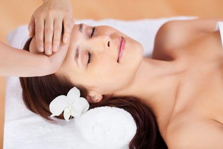 facial: Beautiful fresh woman having facial massage in spa centre