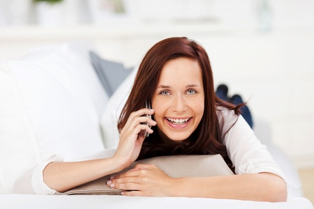 Laughing woman with a mobile phone relaxing on her stomach on a sofa photo
