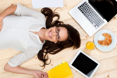 Wood work: Lying female with laptop, digital tablet and food on the floor Stock Photo