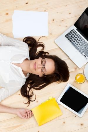 chillen: Porträt der schlafenden Frau auf dem Boden mit Unterlagen, Laptop und digitalen Tablette