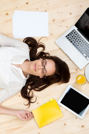 long life: Portrait of sleeping woman on the floor with documents, laptop and digital tablet Stock Photo