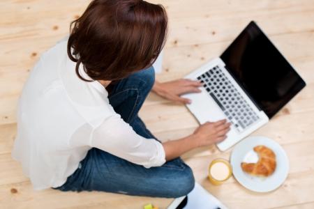 trompo de madera: Mujer en el suelo navegar en su computadora port�til con la comida en el lado Foto de archivo