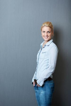 Portret van een lachende jonge vrouw tegen de grijze achtergrond Stockfoto