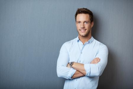 灰色の背景に対して立っているスマートの笑みを浮かべての若い男の肖像