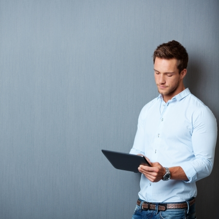 ebook: Serious young male executive using digital tablet against gray background Stock Photo