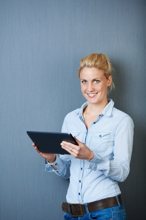 Smiling young female executive using digital tablet against gray background photo