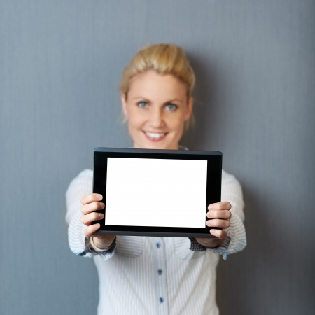 Portrait of a smiling young businesswoman presenting digital tablet against gray background photo