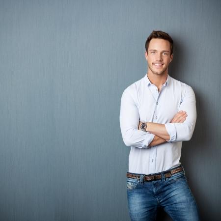 Portret van een slimme jonge man die met de armen gekruist tegen de grijze achtergrond Stockfoto