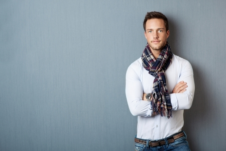 modelos hombres: Retrato de un hombre joven elegante que llevaba una bufanda de pie con los brazos cruzados contra el fondo azul