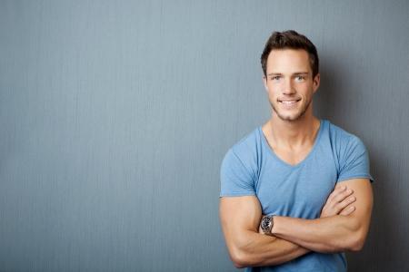 Lachende jonge man met armen gekruist tegen een grijze achtergrond Stockfoto