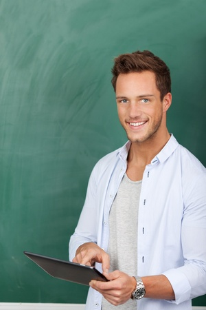 Smiling young male student with tablet pc against green chalkboard photo