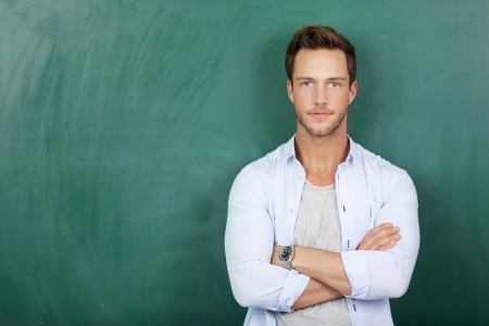 Portrait of a serious young man standing against green chalkboard photo