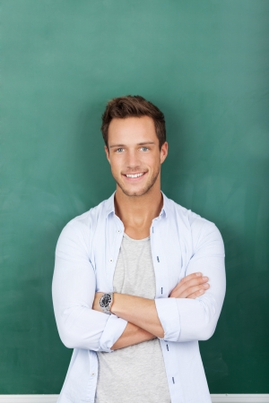 Portrait of a smiling young male teacher standing against green chalkboard photo