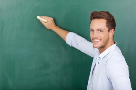 college professor: Portrait of a young man writing on chalkboard Stock Photo