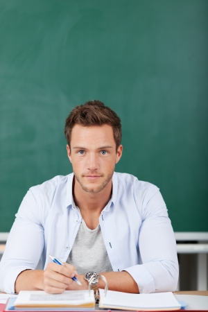 Portrait of a serious young man sitting with folder in front of chalkboard photo