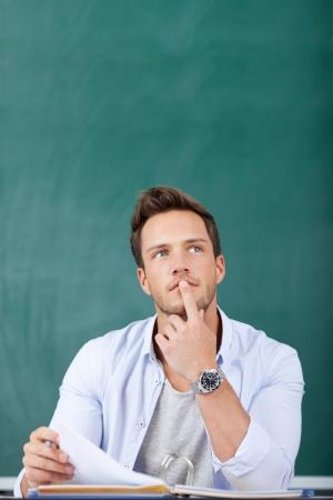 턱에 손가락으로 칠판 앞에 앉아 사려 깊은 젊은 남자 스톡 콘텐츠