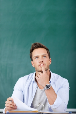 Thoughtful young man sitting in front of chalkboard with finger on chin Фото со стока