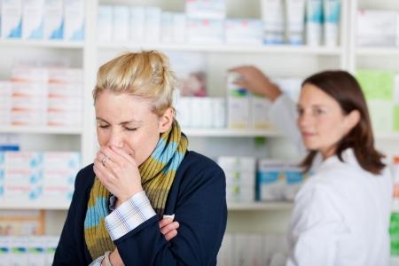 estornudo: Enfermo joven rubia toser con un farmacéutico en la farmacia borrosa en el fondo