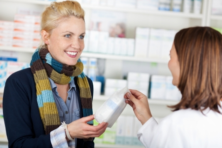 Smiling female customer buying medicine at the pharmacy photo
