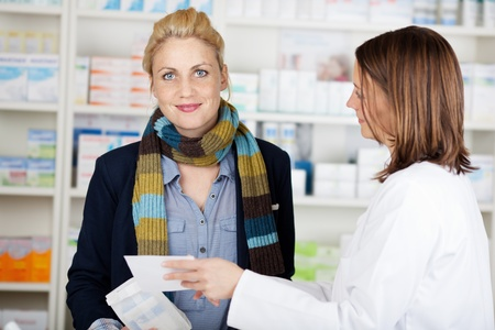 Portrait of a smiling female customer buying medicine at the pharmacy photo