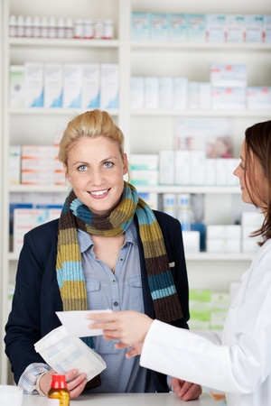 Portrait of a female customer buying medicine at the pharmacy photo