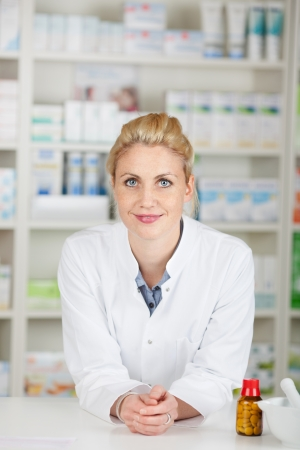 Portrait of a serious blond female pharmacist at drugstore photo