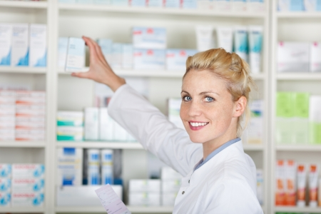 前に薬局で薬の処方の笑みを浮かべて女性薬剤師の肖像画 写真素材