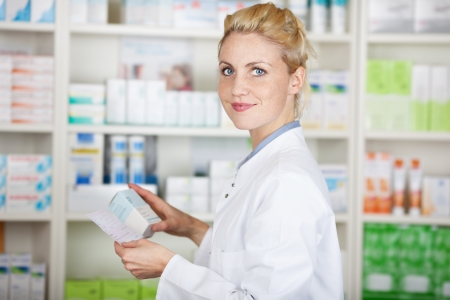 Portrait of a female pharmacist with prescription in front of medicines at drugstore photo