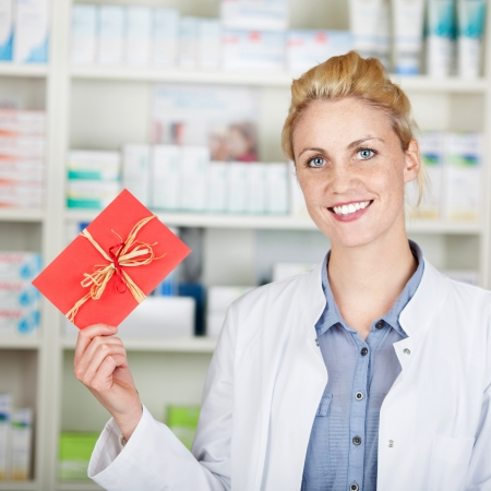 Portrait of a young smiling female pharmacist holding out gift coupon at drugstore photo