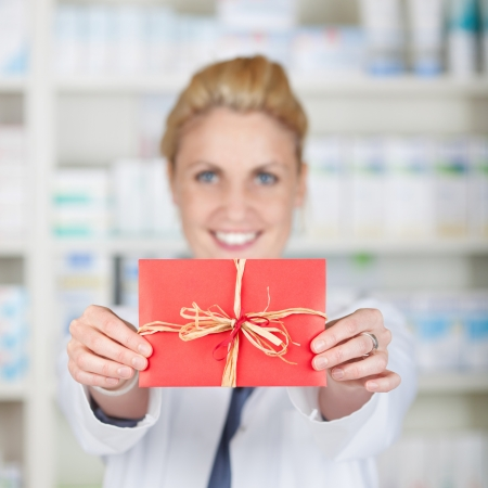 Portrait of a smiling female pharmacist holding out gift coupon at drugstore photo