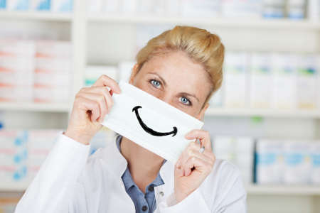 Portrait of a smiling female pharmacist holding happy smiley at drugstore photo