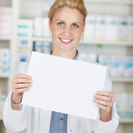 Portrait of a smiling female pharmacist holding blank paper at drugstore photo