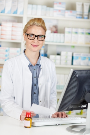 Young smiling female pharmacist with prescription at the drugstore photo